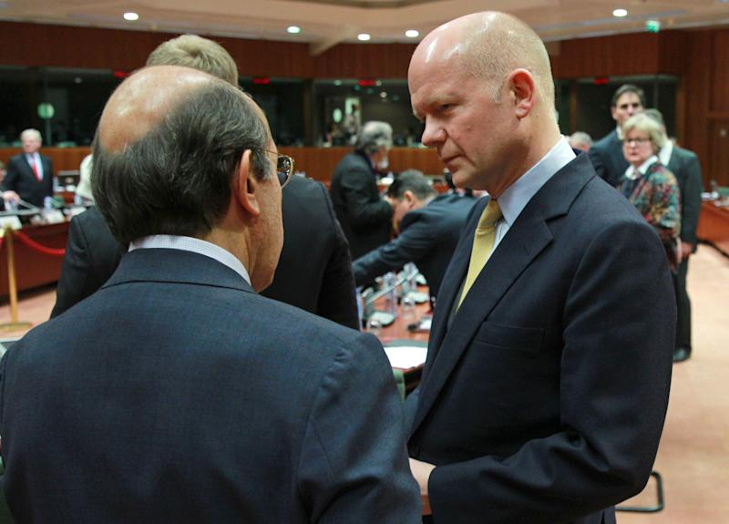 British Foreign Secretary William Hague, right, talks with Spain's ambassador to the EU Jose Pascual Marco Martinez, prior to an extraordinary foreign ministers meeting on Ukraine, at the European Council building in Brussels, Thursday, Feb. 20, 2014. The 28-nation European Union holds an emergency meeting on Ukraine, to consider sanctions against those behind the violence. (AP Photo/Yves Logghe)