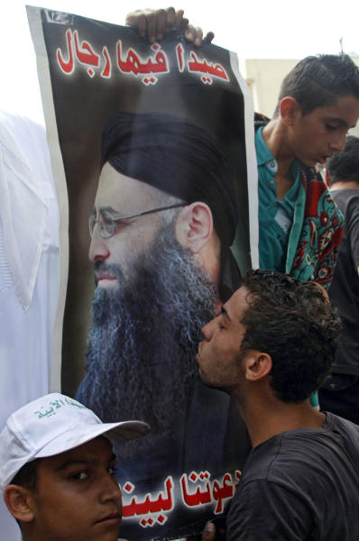 """A Lebanese protester kisses a poster of hard-line Sunni cleric Sheik Ahmad al-Assir with the Arabic reading, """"There are men in Sidon. Anytime you call us we will respond,"""" during a demonstration after the Friday prayer in the southern port city of Sidon, Lebanon, Friday, June 28, 2013. Lebanese troops have fired in the air to disperse dozens of Sunni Muslims demonstrating in support of a hard-line cleric who has been on the run since the military crushed his fighters earlier this week. (AP Photo/Mohammed Zaatari)"""