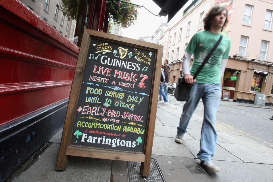 A man walks past a sign outside a pub in Temple Bar in Dublin.