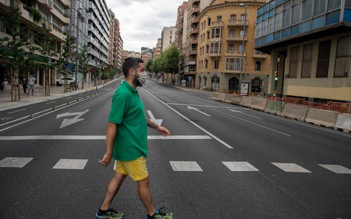 A man with a protective face mask crosses the empty streets of Lleida, Catalonia - RAMON GABRIEL/EPA-EFE/Shutterstock/Shutterstock