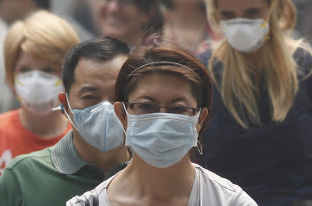 People wearing masks cross a street in Singapore's Orchard Road Shopping Area in this June 21, 2013 file photograph. REUTERS/Edgar Su/Files