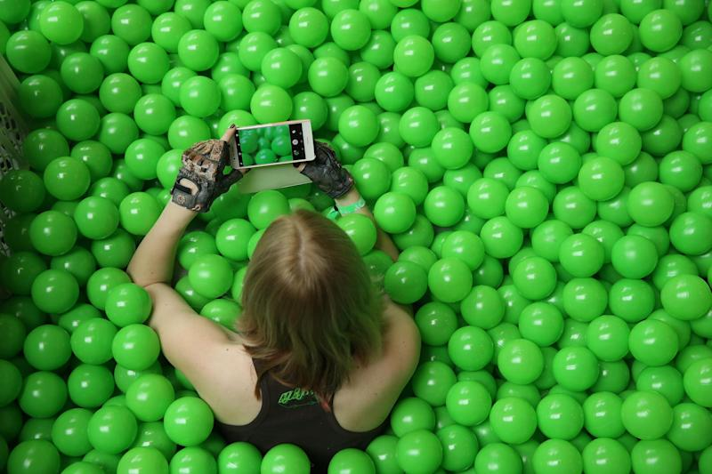 A participant uses her smartphone to photograph the green plastic balls pool she is sitting in at the annual re:publica conferences on their opening day on May 2, 2018 in Berlin, Germany: Sean Gallup/Getty Images