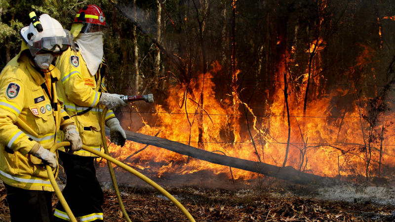 A Tea Gardens RFS crew member Noel Quince and Ralph Clark work on a fire along Timber Tops Drive at Darawank near Forster, Sunday, October 27, 2019. Almost 1200 firefighters are tackling large bushfires on the NSW mid-north coast among scores of blazes around the state. (AAP Image/Darren Pateman) NO ARCHIVING