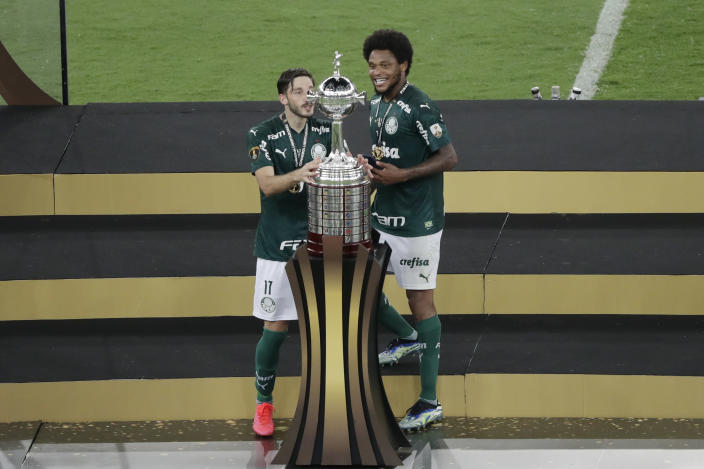 Rony of Brazil's Palmeiras, left, and teammates Luiz Adriano look at the trophy after beating 1-0 Brazil's Santos in the Copa Libertadores final soccer match at the Maracana stadium in Rio de Janerio, Brazil, Saturday, Jan. 30, 2021. (AP Photo/Silvia Izquierdo)