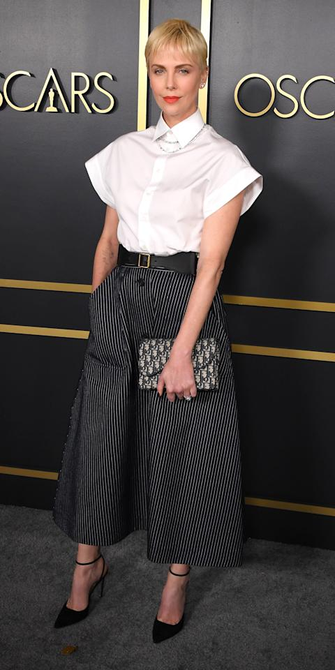 <p>Charlize Theron posed at the Oscars nominee luncheon in a Dior blouse, striped skirt, and logo-embellished clutch.</p>