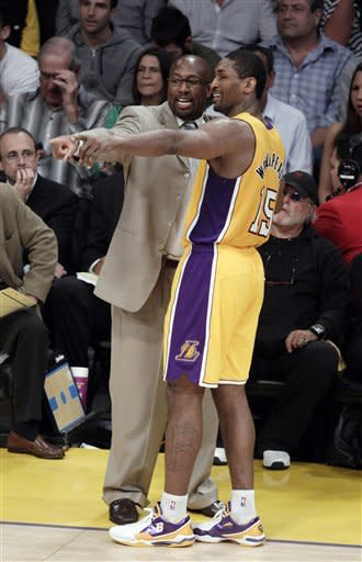 Los Angeles Lakers head coach Mike Brown, left, talks with Metta World Peace during the first half in Game 4 of an NBA basketball playoffs Western Conference semifinal game against the Oklahoma City Thunder in Los Angeles, Saturday, May 19, 2012. (AP Photo/Jae C. Hong)