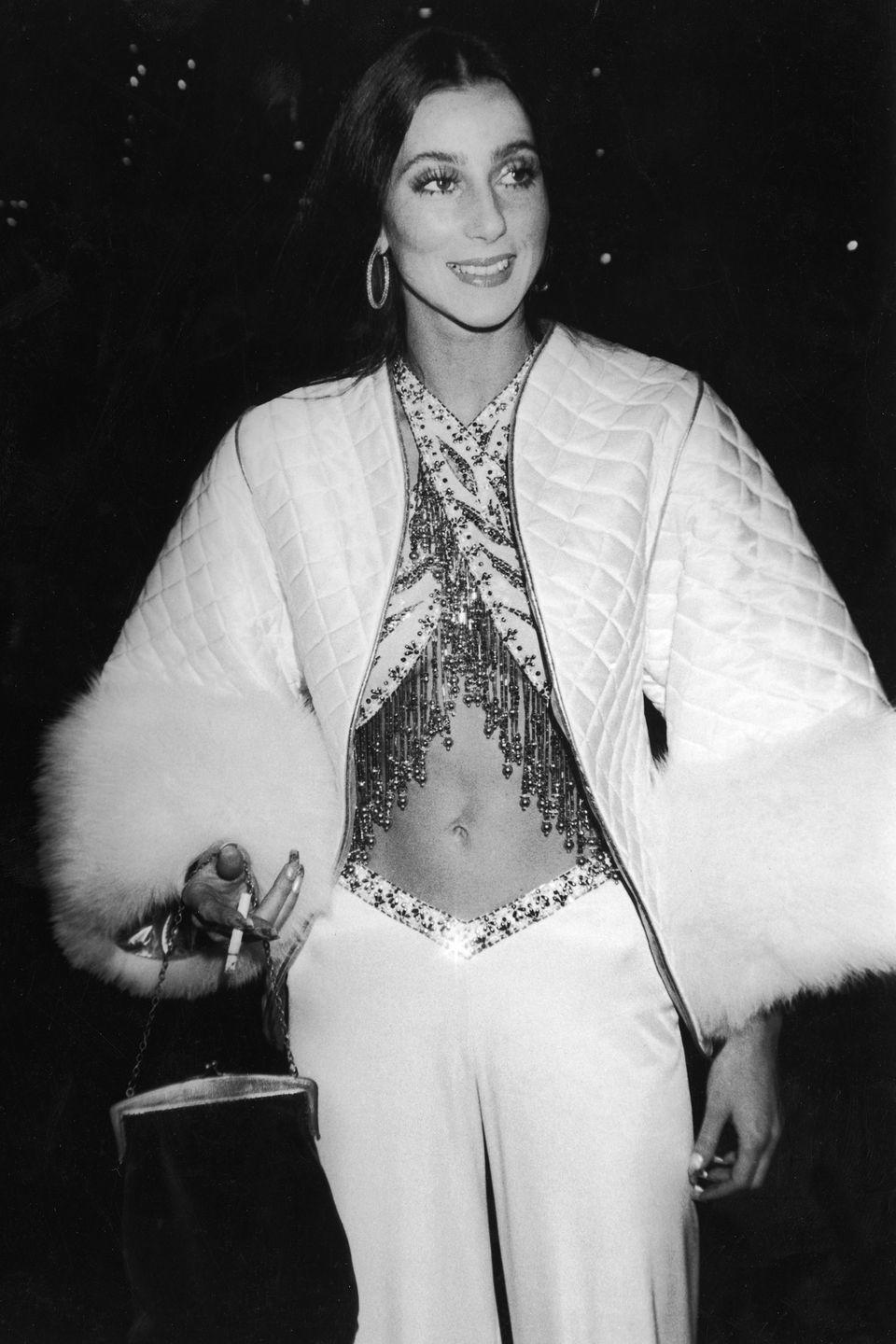 <p>She holds a cigarette while posing in crisscrossed sequined halter top and a fur-trimmed quilted coat.</p>