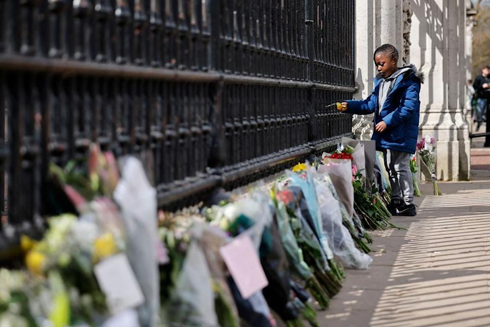 A boy adds to floral tributes against the railings at the front of Buckingham Palace