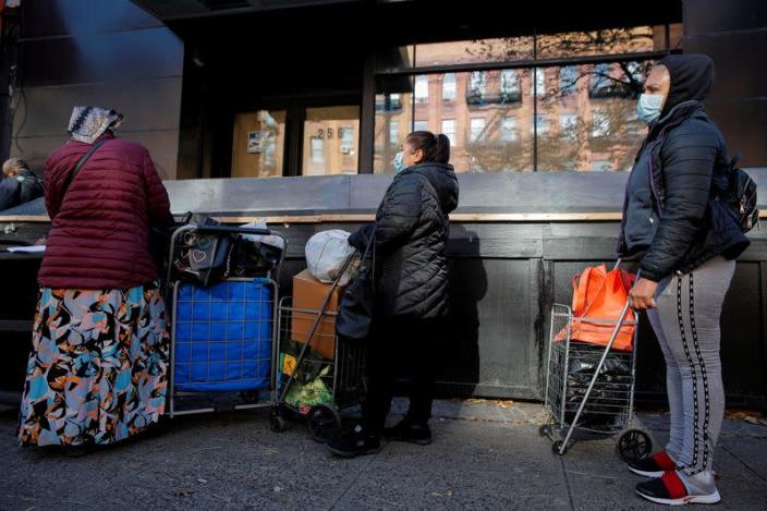 People line up to receive free holiday boxes of food ahead of the Thanksgiving holiday in New York
