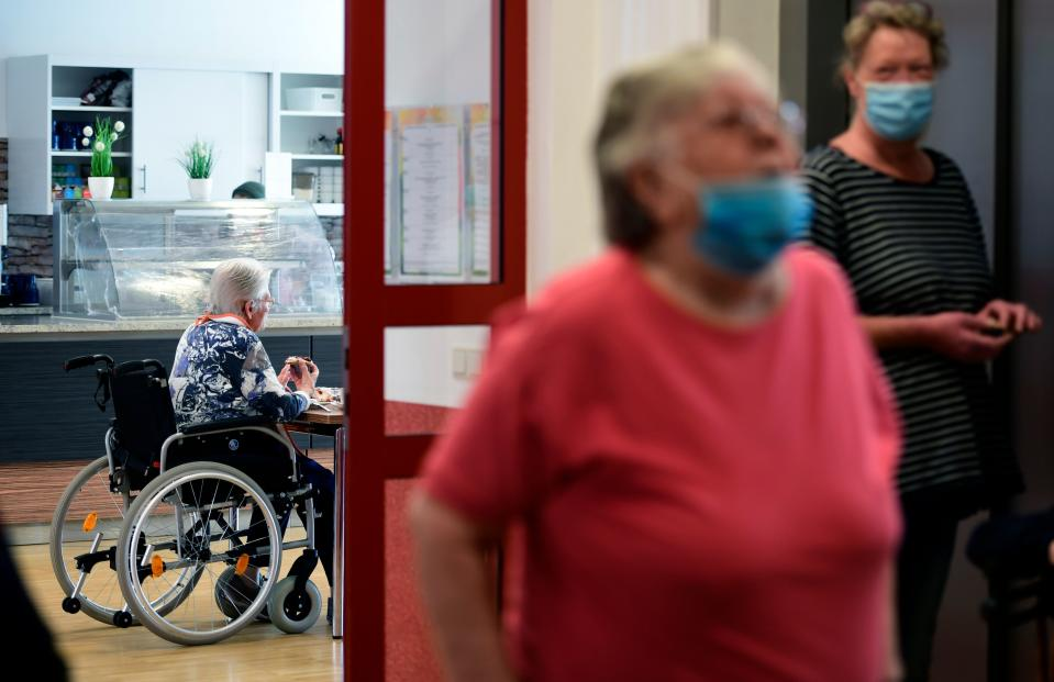 A resident sits at a table in the cafeteria of the retirement home 'CBT-Wohnhaus Zur Heiligen Familie' in Duesseldorf, western Germany on May 13, 2020 amid the ongoing Covid-19, coronavirus pandemic. - North Rhine-Westphalia's Health Minister Karl-Josef Laumann visited a Caritas nursing home in Duesseldorf. On site, he would like to get an idea of how the nursing staff and the home management made the first visits possible after the corona-related visit prohibitions for elderly people. (Photo by Ina FASSBENDER / AFP) (Photo by INA FASSBENDER/AFP via Getty Images)