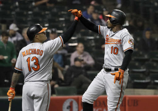 Baltimore Orioles' Adam Jones (10) celebrates his home run off Chicago White Sox's Hector Santiago with Manny Machado (13) during the sixth inning of a baseball game Monday, May 21, 2018, in Chicago. (AP Photo/Charles Rex Arbogast)