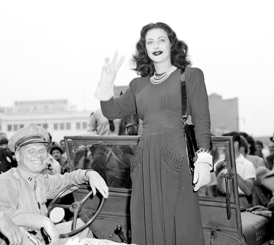 <p>Hedy Lamarr gives the V-for-Victory sign while selling war bonds in Newark, New Jersey, wearing a dress with boxy shoulders that is nipped at the waist. </p>