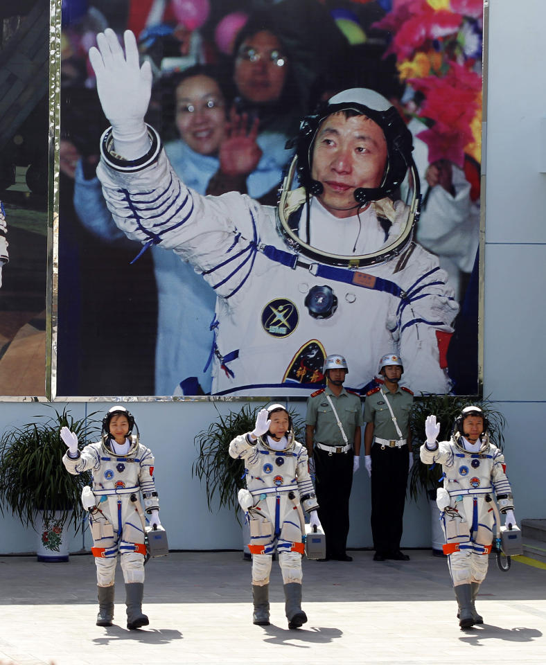 China's astronauts from left., Liu Yang, Jing Haipeng and Liu Wang wave and walk before a giant portrait of China's first astronaut Yang Liwei, as they depart for the Shenzhou 9 spacecraft rocket launch pad at the Jiuquan Satellite Launch Center in Jiuquan, China, Saturday, June 16, 2012. China will send its first woman and two other astronauts into space Saturday to work on a temporary space station for about a week, in a key step toward becoming only the third nation to set up a permanent base in orbit.(AP Photo/Ng Han Guan)