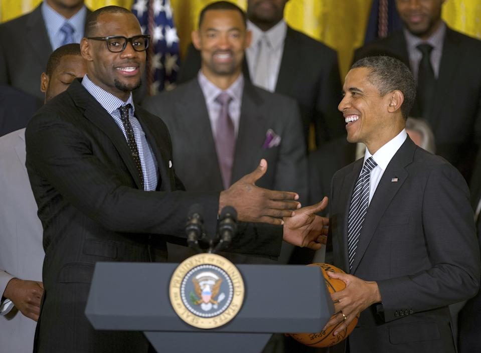 LeBron James in a suit and tie next to Barack Obama at the president's podium in the White House.