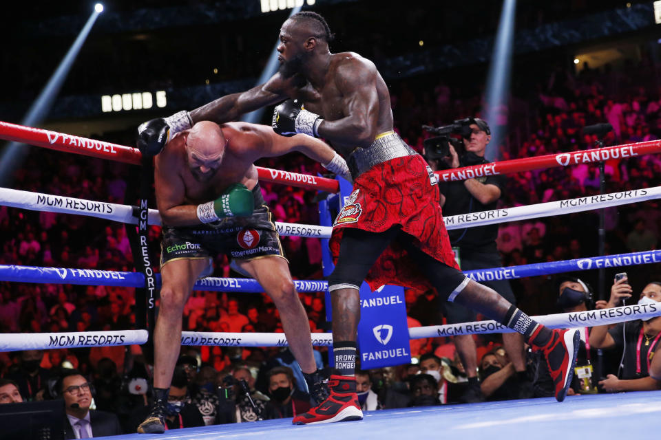 Deontay Wilder swings at Tyson Fury, of England, in a heavyweight championship boxing match Saturday, Oct. 9, 2021, in Las Vegas. (AP Photo/Chase Stevens)