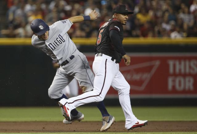 Arizona Diamondbacks third baseman Eduardo Escobar (5) tags out San Diego Padres' Ian Kinsler, left, during a rundown in the second inning of a baseball game Saturday, April 13, 2019, in Phoenix. (AP Photo/Ross D. Franklin)
