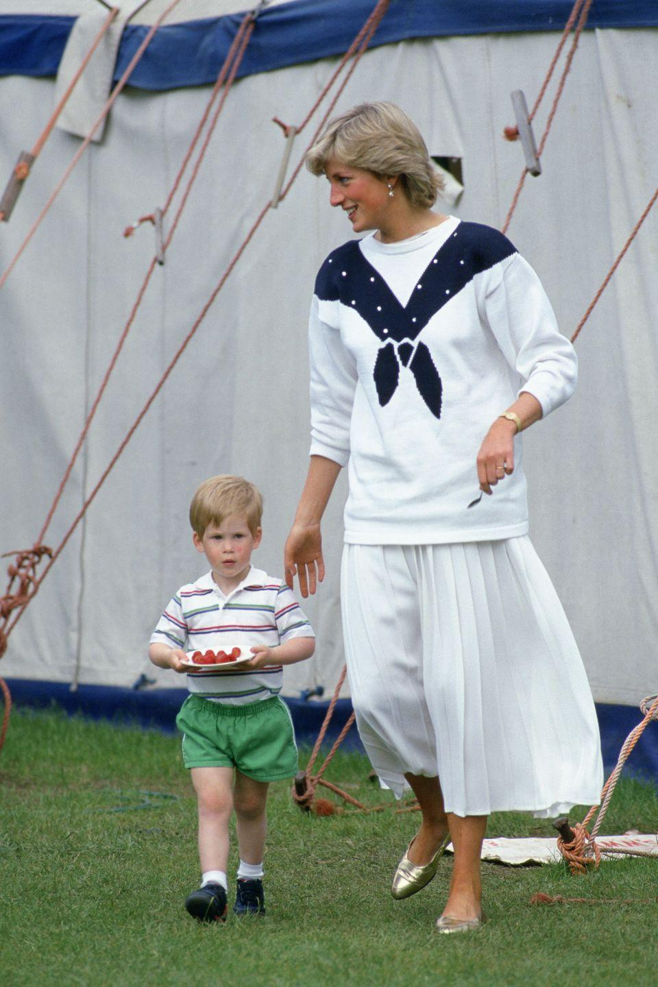 <p>Diana photographed alongside a toddling Harry, who's carrying a plate of strawberries</p>
