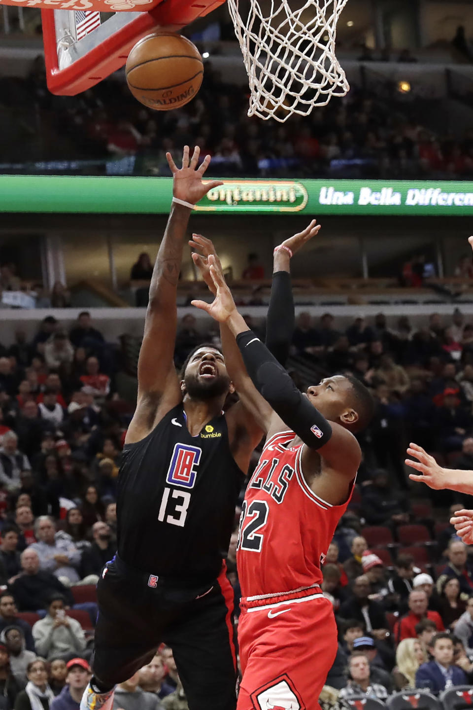 Los Angeles Clippers forward Paul George, left, and Chicago Bulls forward Kris Dunn battle for a loose ball during the first half of an NBA basketball game Saturday, Dec. 14, 2019, in Chicago. (AP Photo/Nam Y. Huh)