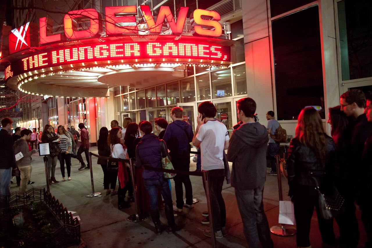 "Fans line up to see the midnight shows of ""The Hunger Games,"" at the 34th Street Loews AMC Theatre, Thursday, March 22, 2012, in New York. The film, about children who are forced to compete in a live televised death match in the not-too-distant future, is based on the popular young adult book series by Suzanne Collins. (AP Photo/John Minchillo)"