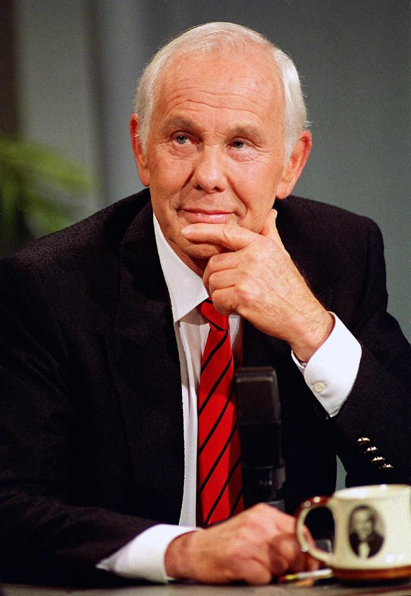 """FILE - This May 22, 1992 file photo shows talk show host Johnny Carson, with his personalized coffee cup in front of him, watching clips from earlier shows during the last taping of the """"Tonight Show"""" in front of family and friends in Burbank, Calif.  (AP Photo/Douglas C. Pizac, file)"""