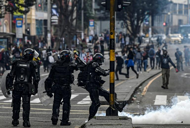 A riot policeman kicks a tear-gas canister during an anti-government protest in Bogota on November 23, 2019
