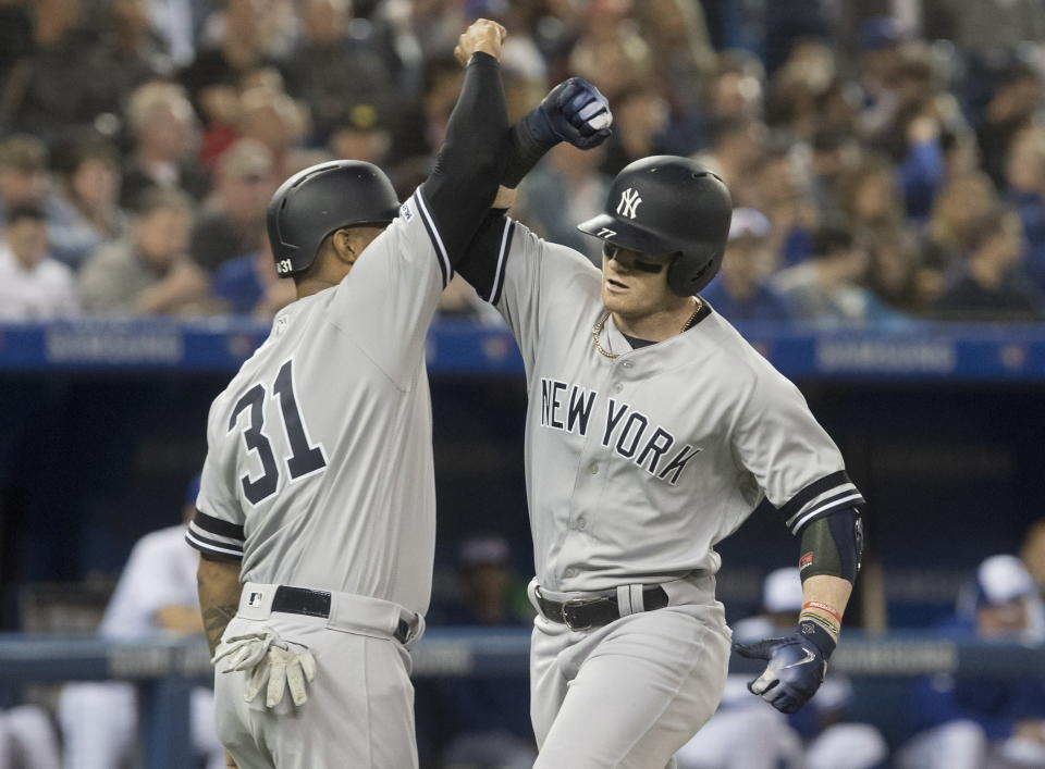 New York Yankees' Clint Frazier met by Aaron Hicks, left, at home plate after hitting a two-run home run, on which Hicks scored, in the fourth inning of a baseball game against the Toronto Blue Jays in Toronto on Tuesday, June 4, 2019. (Fred Thornhill/The Canadian Press via AP)