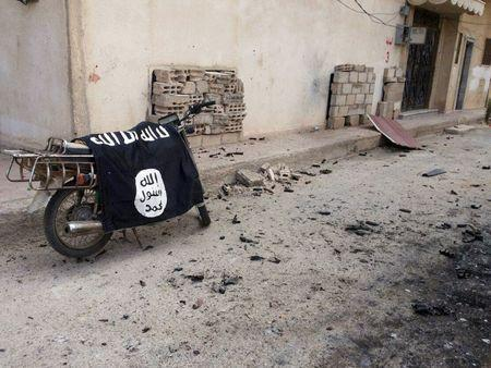 A flag belonging to the Islamic State fighters is seen on a motorbike after forces loyal to Assad recaptured the historic city of Palmyra