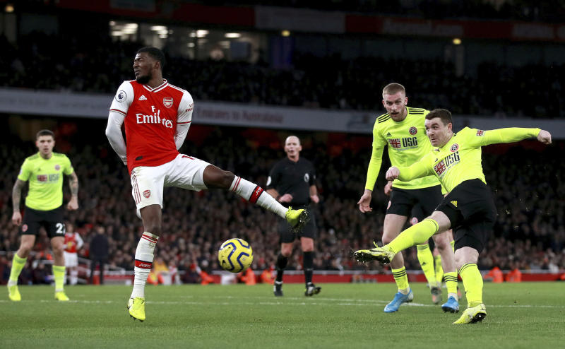 Sheffield United's John Fleck, right, scores his sides first goal past Arsenal's Ainsley Maitland-Niles during the English Premier League soccer match between Arsenal and Sheffield United at the Emirates Stadium, London, Saturday, Jan. 18, 2020. (Adam Davy/PA via AP)