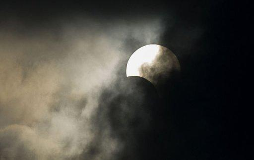 An annular solar eclipse is seen through clouds in Hong Kong on May 21. A few thousand optimistic early birds gathered on the Victoria Harbour waterfront in Hong Kong hoping to catch a glimpse of the spectacle, but heavy cloud cover gave them only a brief window of less than a minute