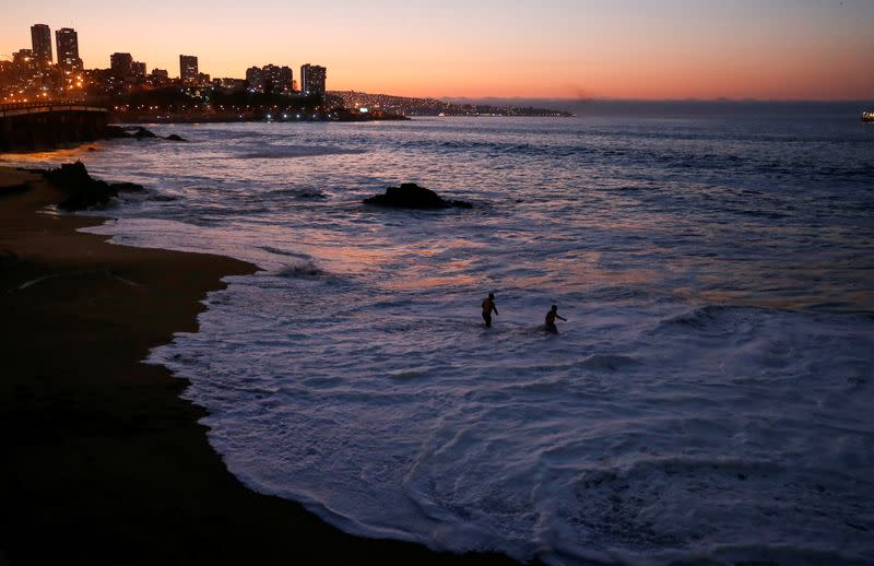 People are seen on a beach as the national emergency office, ONEMI, through a message on Chileans' cell phones, urges people to abandon coastal areas after a quake at the Chilean Antarctic territory, in Vina del Mar