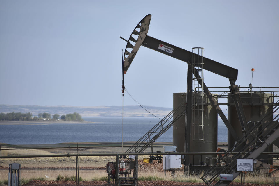 In this Wednesday, May 19, 2021, photo, a pump jack extracts oil from beneath the ground on the Fort Berthold Indian Reservation, with Lake Sakakawea in the background, east of New Town, North Dakota. About half of the 16,000 members live on the Fort Berthold Indian Reservation atop one of the biggest U.S. oil discoveries in decades. (AP Photo/Matthew Brown)
