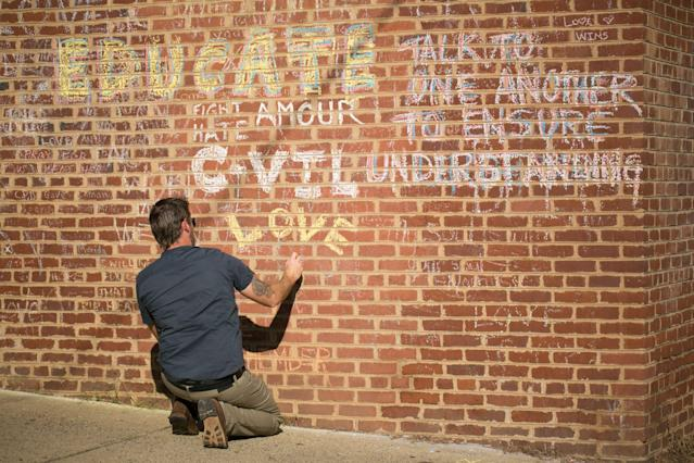 <p>A man adds on August 10, 2018 to the hand-written chalk messages that line the walls outside of the buildings where one year ago, Heather Heyer was killed by a speeding vehicle driven by a white supremacist as she was protesting the Unite The Right rally in Charlottesville, Va. (Photo: Logan Cyrus/AFP/Getty Images) </p>
