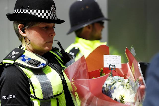 <p>A police officer carries a bunch of flowers with a note near Borough Market in London, June 4, 2017. (Photo: Peter Nicholls/Reuters) </p>