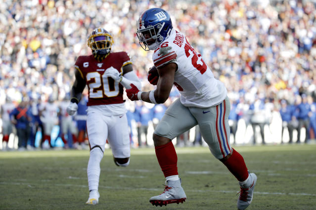 New York Giants running back Saquon Barkley, right, catches a touchdown pass from quarterback Daniel Jones, not visible, as Washington Redskins strong safety Landon Collins (20) tries to defend during the first half of an NFL football game, Sunday, Dec. 22, 2019, in Landover, Md. (AP Photo/Patrick Semansky)