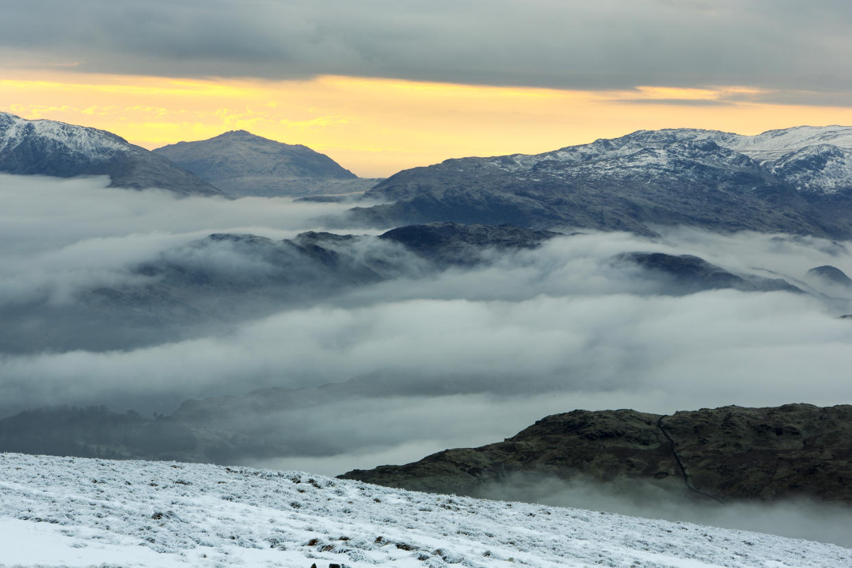 Red Screes above Ambleside with mist from a temperature inversion, Lake District, UK, looking towards Harter Fell.