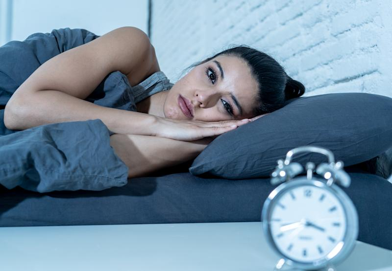 Sleepless and desperate beautiful latin woman awake at night not able to sleep looking at clock suffering from insomnia in sleep disorder concept.