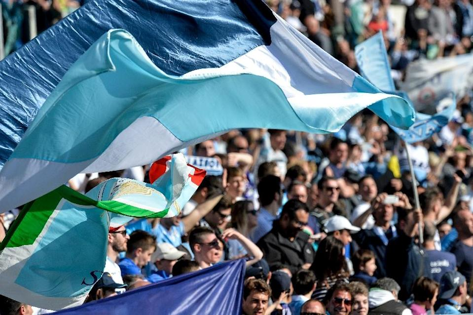 Lazio's fans wave flags at the end of the Italian Serie A football match Lazio vs Empoli on April 12, 2015 at Rome's Olympic stadium (AFP Photo/Andreas Solaro)