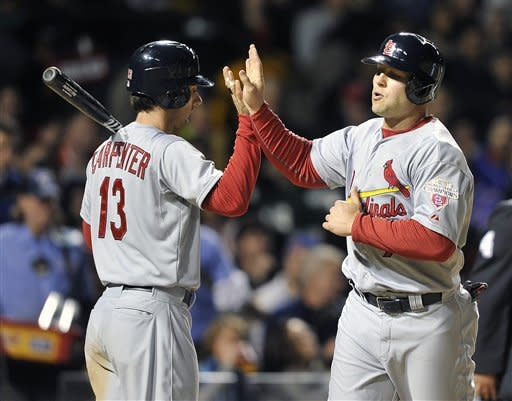 St. Louis Cardinals' Matt Carpenter (13) high-fives Matt Holliday after Holliday scored on a sacrifice fly by Yadier Molina during the fourth inning of a baseball game against the Chicago Cubs on Monday, April 23, 2012, in Chicago. (AP Photo/Jim Prisching)