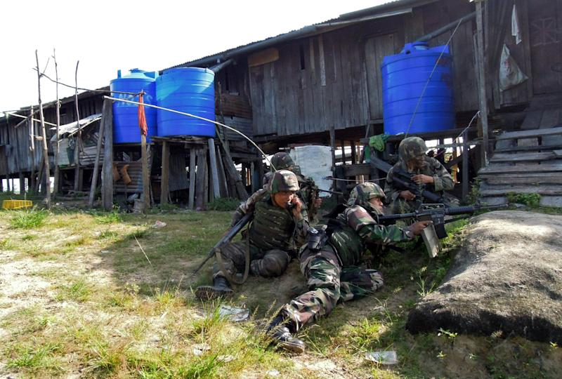 In this Tuesday, March 5, 2013 photo released by Malaysia's Ministry of Defense, Malaysian soldiers join an assault near the area where a stand-off with Filipino gunmen took place, at Tanduo village in Lahad Datu, Borneo's Sabah state, Malaysia. Malaysian security forces on Wednesday, March, 6, 2013 battled a group of Filipino intruders in the rugged terrain of Borneo after they escaped a military assault with fighter jets and mortar fire on their hideout, police said. One Filipino was shot and believed killed. (AP Photo/Malaysia's Ministry of Defense) EDITORIAL USE ONLY, NO SALES