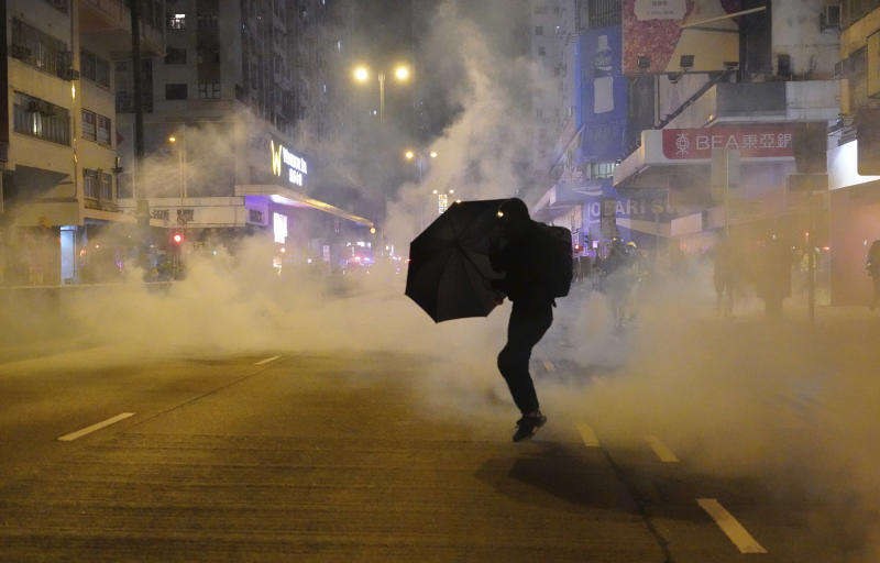 FILE - In this Jan. 1, 2020, file photo, a protester holds an umbrella as police fire tear gas during a demonstration in Hong Kong. The human rights group Amnesty International says in annual report released Wednesday, Jan. 29, 2020 that while authoritarian controls are increasingly undermining freedoms in Asia, the will to resist such repression is also growing. (AP Photo/Vincent Yu, File)