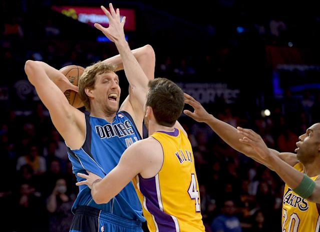 Dallas Mavericks forward Dirk Nowitzki, left, of Germany, is double-teamed by Los Angeles Lakers forward Ryan Kelly (4) and guard Jodie Meeks, right, during the first half of an NBA basketball game, Friday, April 4, 2014, in Los Angeles.(AP Photo/Gus Ruelas)