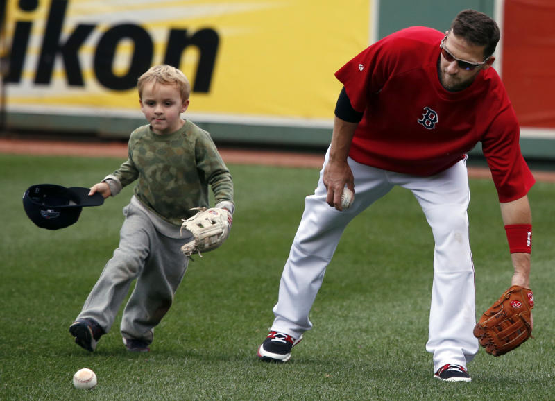 Boston Red Sox's Stephen Drew, right, catches balls with his son Hank during a baseball team workout at Fenway Park in Boston, Thursday, Oct. 10, 2013, in preparation for Game 1 of the ALCS, Saturday. (AP Photo/Elise Amendola)
