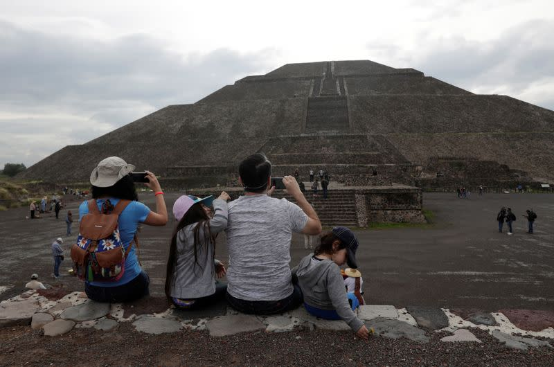 Members of a family take pictures with their cell phones as they wear protective masks during the start of the gradual reopening of the ancient ruins of Teotihuacan