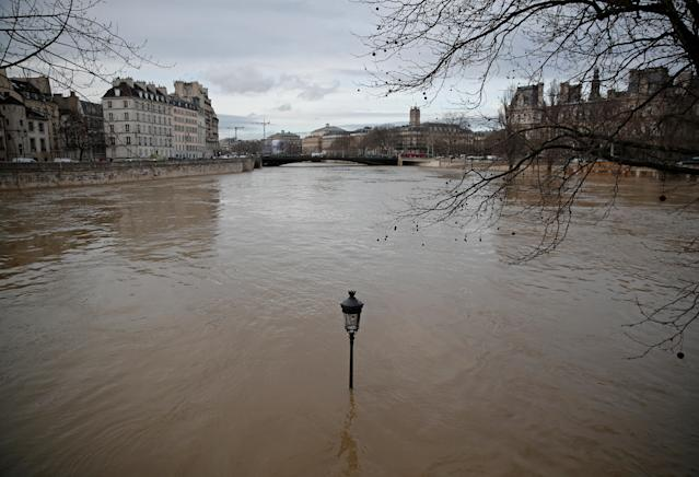 <p>A street-lamp is seen on the flooded banks of the Seine River in Paris, France, after days of almost non-stop rain caused flooding in the country, Jan. 24, 2018. (Photo: Christian Hartmann/Reuters) </p>