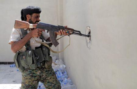 A member of the Syrian Democratic Forces widens the hole in the wall during the fighting with Islamic State in Al Senaa, a district of Raqqa, Syria, August 10, 2017. REUTERS/Zohra Bensemra