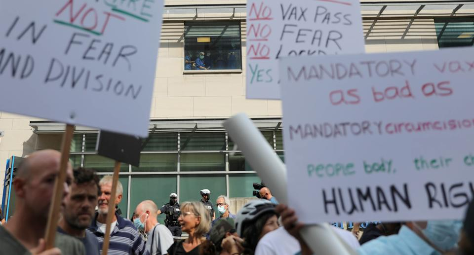Health workers look at an anti-vaccine mandate protest outside Toronto General Hospital in Toronto, Ontario, Canada September 13, 2021.  REUTERS/Chris Helgren