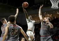 Miami guard Anthony Lawrence II, center, goes to the basket against Boston College forward Nik Popovic, right, in the first half of an NCAA college basketball game in Coral Gables, Fla., Saturday, Feb. 24, 2018. (Pedro Portal/Miami Herald via AP)