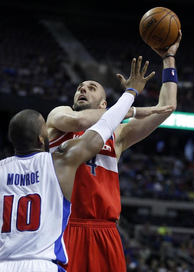 Washington Wizards center Marcin Gortat (4) takes a shot against Detroit Pistons center Greg Monroe (10) during the first half of an NBA basketball game, Monday, Dec. 30, 2013, in Auburn Hills, Mich. (AP Photo/Duane Burleson)