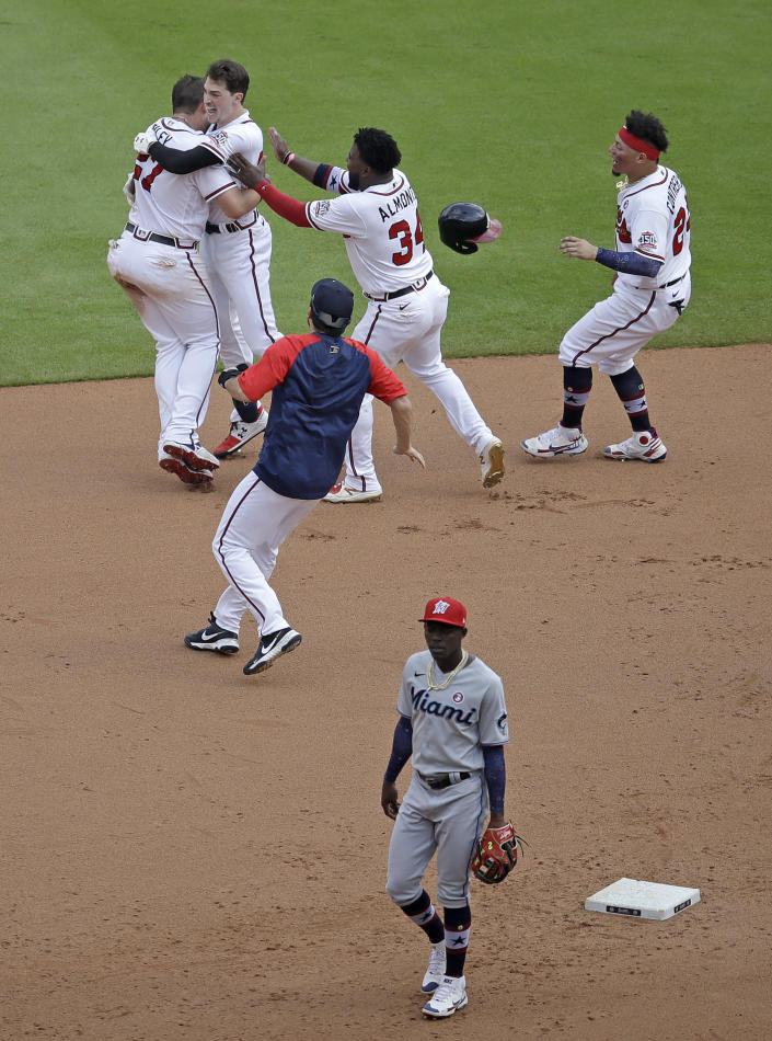 Atlanta Braves' Max Fried, second from top left, is mobbed by teammates after making the winning hit against the Miami Marlins during the 10th inning of a baseball game Sunday, July 4, 2021, in Atlanta. (AP Photo/Ben Margot)