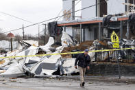 FILE - In this March 3, 2020, file photo, a man walks past storm debris Tuesday, March 3, 2020, in Nashville, Tenn. It has been nearly a year since deadly tornados tore across Nashville and other parts of Tennessee as families slept. The March 3 storm killed more than 20 people, some in their beds, as it struck after midnight. More than 140 buildings were destroyed across a swath of Middle Tennessee, burying people in rubble and basements. (AP Photo/Mark Humphrey, File)